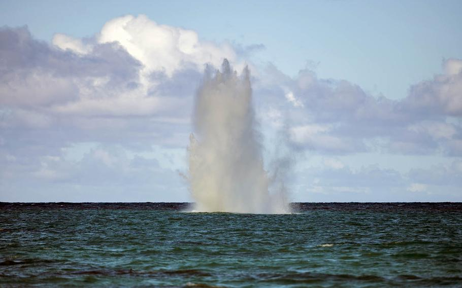 Water erupts just off Lanikai Beach, Oahu, Hawaii, from the controlled detonation of two World War II-era gravity bombs by Navy ordnance experts.