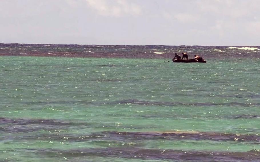 Sailors assigned to Mobile Diving Salvage Unit 1 Detachment use an inflatable dinghy April 27, 2020, as they place an underwater charge to detonate World War II-era bombs found near a popular Oahu, Hawaii, beach.
