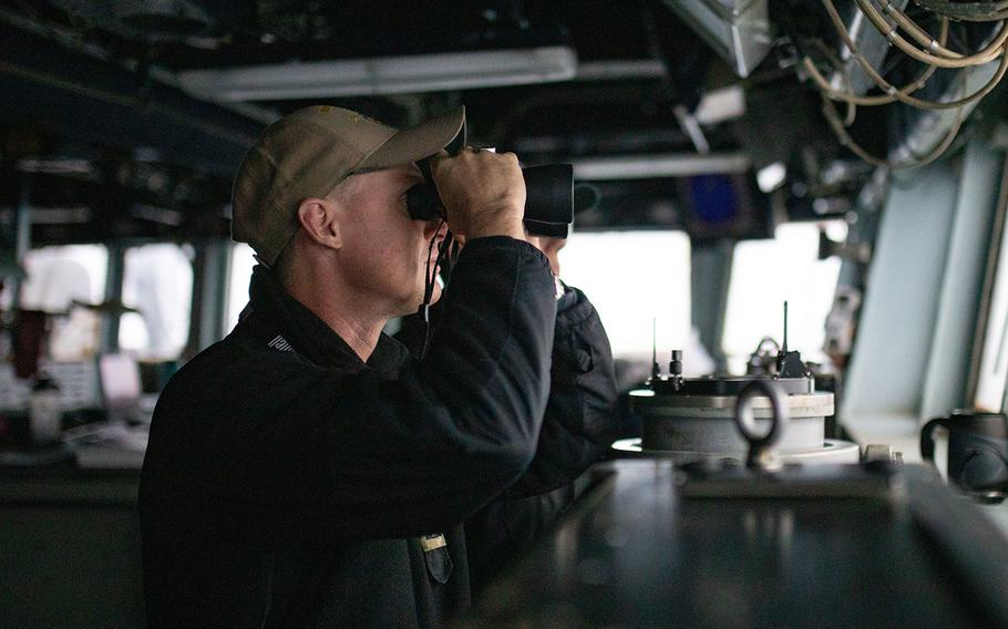 Lt. Richard Burk Vidmar stands watch on the bridge of the guided-missile destroyer USS Barry near the Paracel Islands in the South China Sea, Tuesday, April 28, 2020.