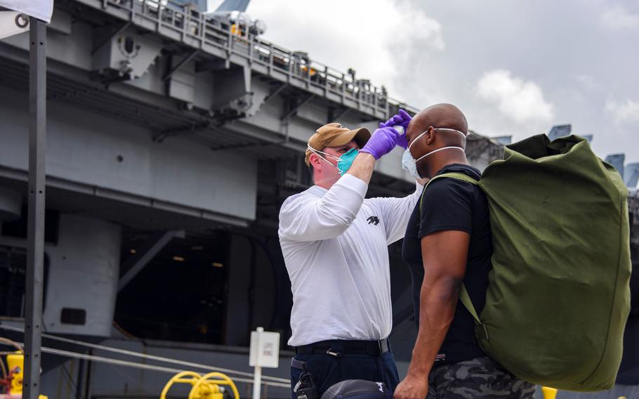 A sailor assigned to the USS Theodore Roosevelt prepares to board the aircraft carrier at Naval Base Guam, Friday, May 1, 2020. Those who have tested negative for the coronavirus, are asymptomatic and have completed their off-ship quarantine or isolation are allowed aboard the ship.