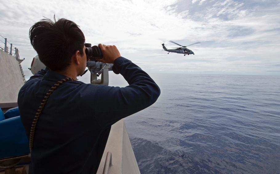 Petty Officer 3rd Class Adolfo Rodriguez of the USS Gabrielle Giffords stands watch as an MH-60S Sea Hawk takes off from the littoral combat ship's flight deck in the South China Sea, April 27, 2020.