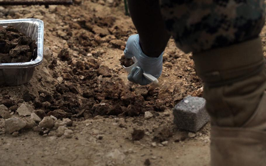 A Marine collect soil samples for Japanese officials, May 1, 2020, where firefighting foam leaked last month at Marine Corps Air Station Futenma, Okinawa.