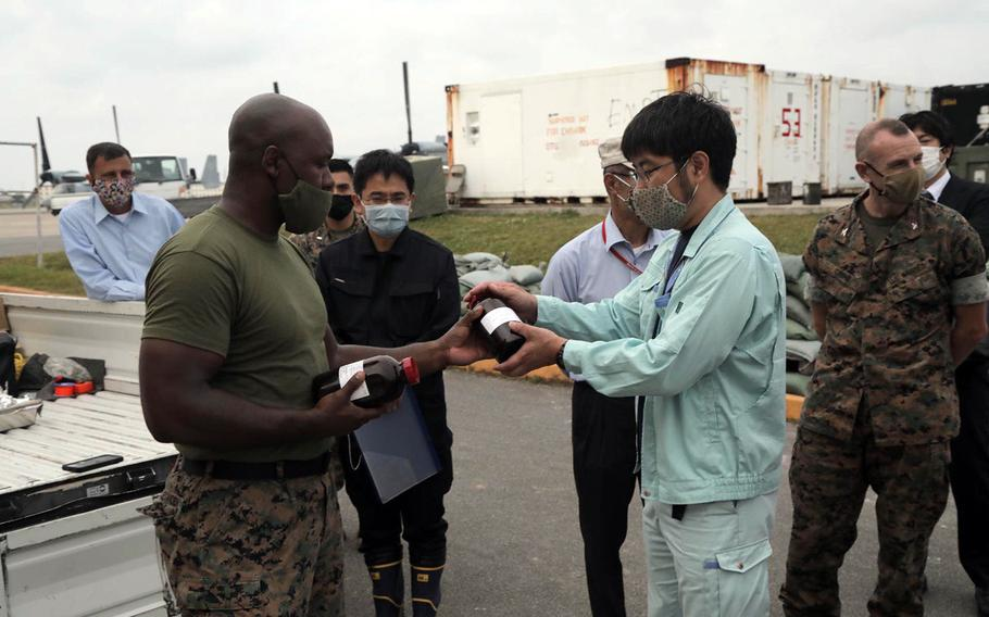A Marine hands soil samples to a Japanese official, May 1, 2020, where firefighting foam leaked last month at Marine Corps Air Station Futenma, Okinawa.