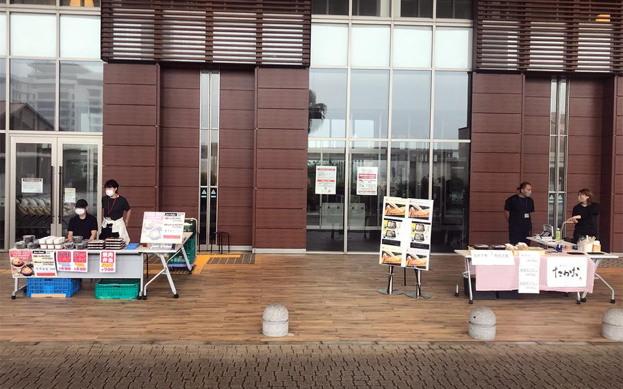 Restaurant workers sell to-go lunch boxes outside Aeon Mall Okinawa Rycom in Kitanakagusuku, Okinawa, Tuesday, May 12, 2020. The mall is closed because of the coronavirus pandemic.