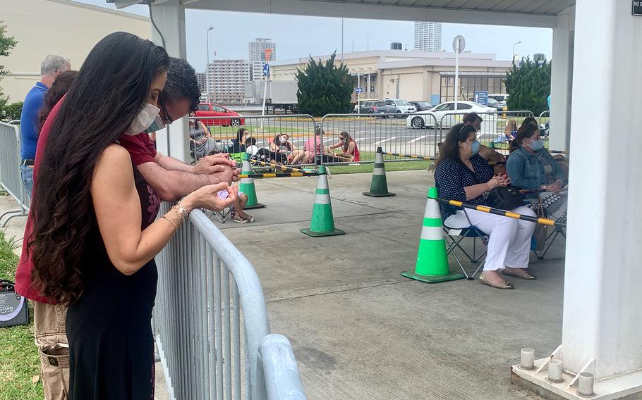 Navy spouse Lori Ann Chavez-Garcia prays with other churchgoers during an outdoor service at Yokosuka Naval Base, Sunday, May, 31, 2020.