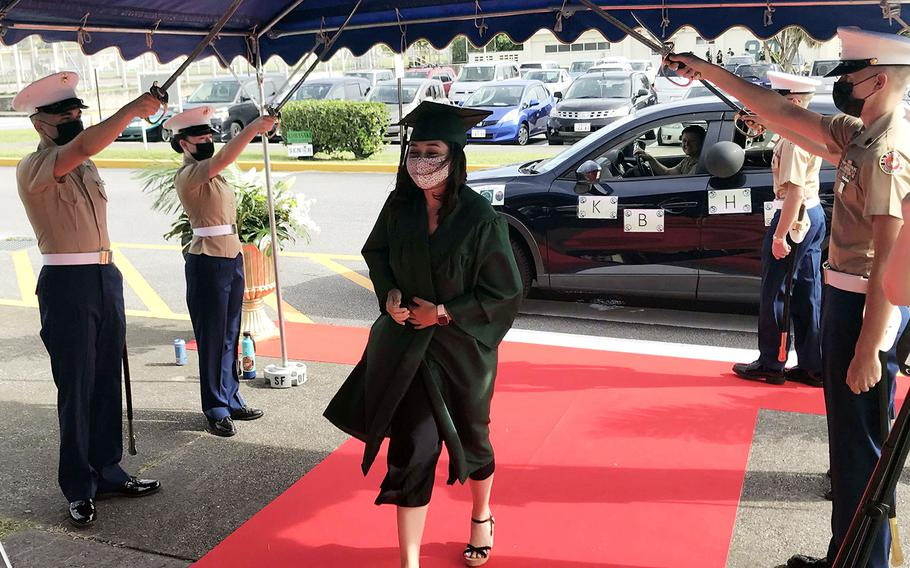 Kubasaki High School senior Tina Davis is saluted with a Marine sabre arch while accepting her diploma during a drive-thru ceremony at Camp Foster, Okinawa, Saturday, June 6, 2020.