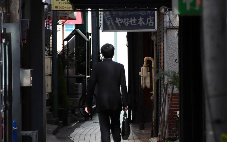 A Japanese salaryman walks through an alleyway in Yokosuka, Japan, April 14, 2020.