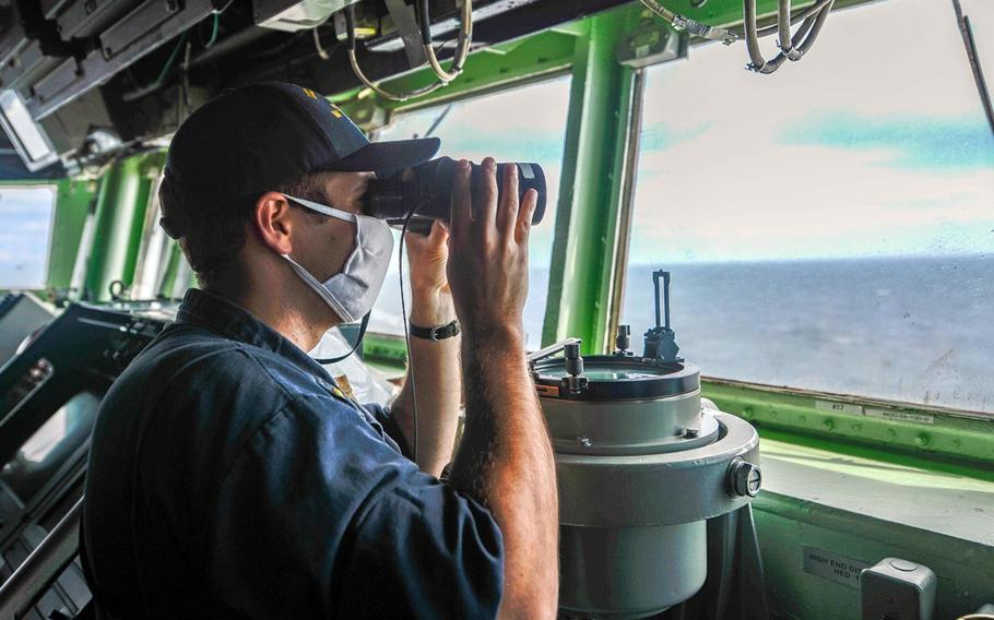 Ensign Ryan O'Neal  searches for surface contacts from the pilot house as the guided-missile destroyer USS Russell sails through the Taiwan Strait, Thursday, June 4, 2020.