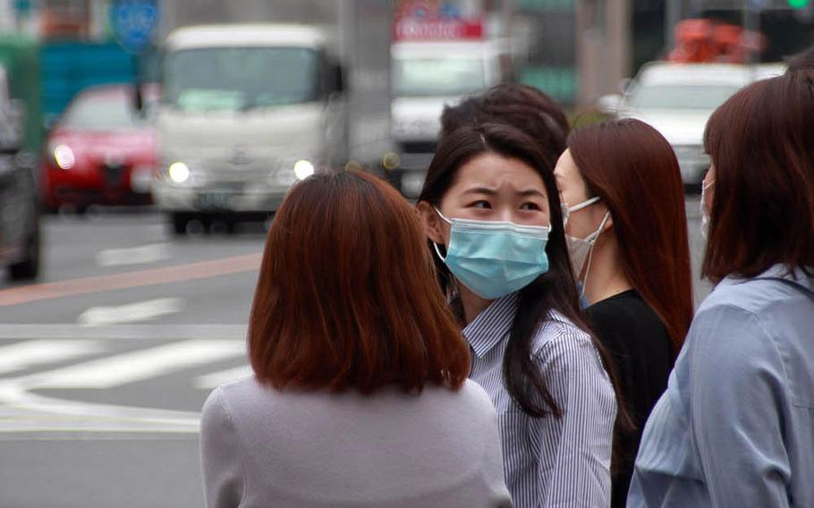 Masked pedestrians wait to cross a street in Tokyo's fashionable Omotesando district, May 22, 2020.