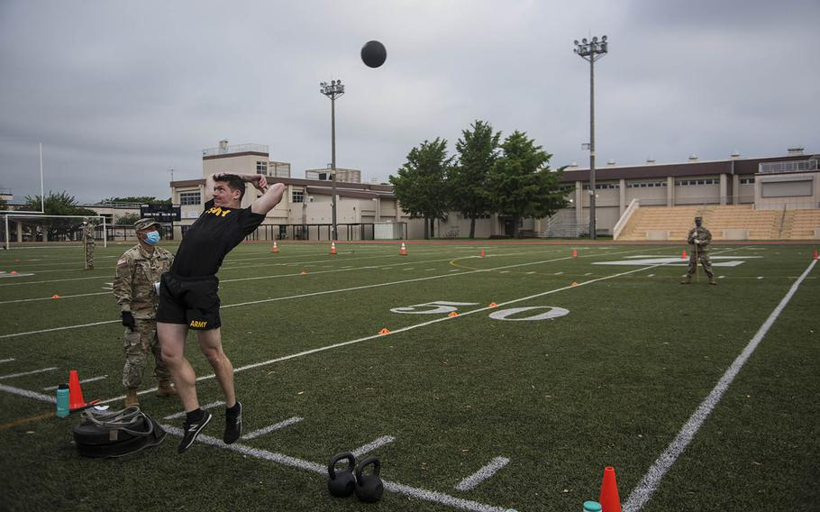 A soldier hurls a 10-pound medicine ball during a combat fitness test competition at Camp Zama, Japan, Monday, June 8, 2020.
