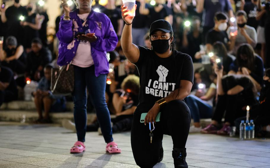 People hold up candles and cellphones during a moment of silence, which lasted nearly nine minutes, to honor George Floyd at Camp Humphreys, South Korea, Thursday, June 11, 2020.