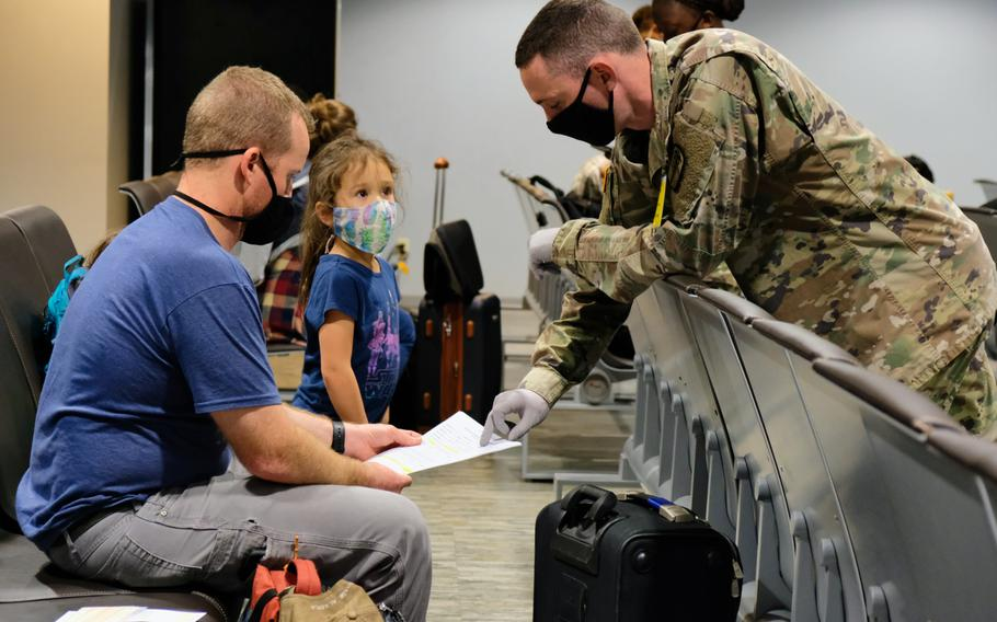 A soldier from the 65th Medical Brigade goes over a coronavirus questionnaire with a passenger arriving at Osan Air Base, South Korea, Wednesday, June 10, 2020.