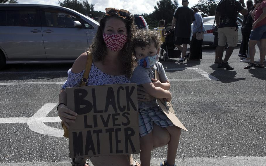 Air Force spouse Sienna Searle holds up a Black Lives Matter sign with son, Ronin, during a vigil at Kadena Air Base, Okinawa, Saturday, June 13, 2020.