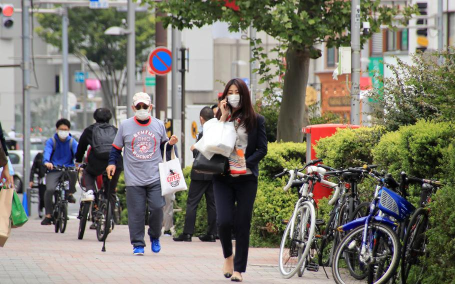 People stroll and shop in Tokyo's Omotesando district during lunch time.