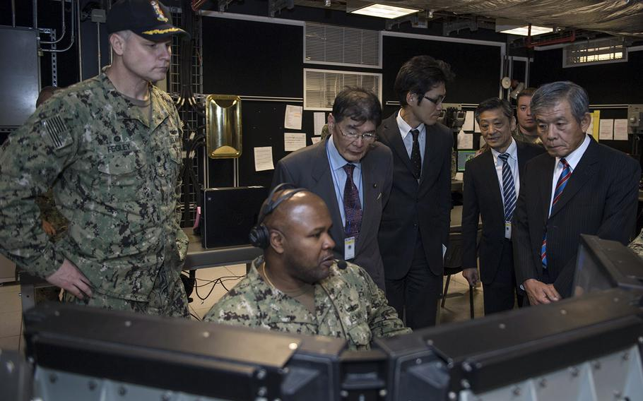 Navy Cmdr. Mark Fegley, left, of Aegis Ashore Missile Defense System Romania gives members of the Japanese Diet Council for Comprehensive Security a tour of the combat information center, Oct. 6, 2017.