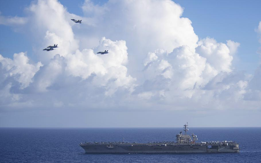 F/A-18 Super Hornets assigned to Carrier Air Wing 11 fly in the missing man formation over the aircraft carrier USS Theodore Roosevelt in the Philippine Sea, June 18, 2020. The formation honored Capt. Rinehart Wilke IV, a former commanding officer for Strike Fighter Squadron 154, who died of cancer in May.