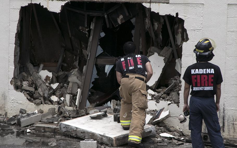 Firefighters survey damage to a hazardous materials building at Kadena Air Base, Okinawa, Tuesday, June 23, 2020, the day after it caught fire.