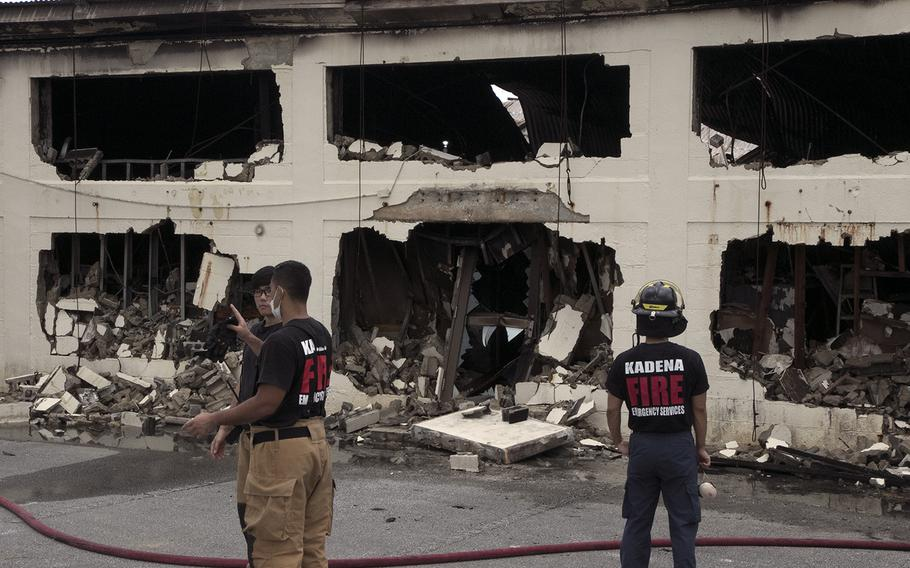 Firefighters survey damage at Kadena Air Base, Okinawa, Tuesday, June 23, 2020, the day after a blaze engulfed a hazardous materials building and released chlorine gas into the air.