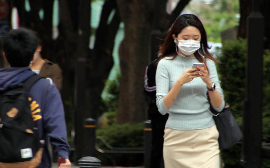 People wear masks as they stroll through the Omotesando district of central Tokyo, May 22, 2020.