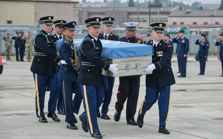 A United Nations Command honor guard carries the remains of six service members killed in the Korean War during a repatriation ceremony at Osan Air Base, South Korea, Friday, June 26, 2020.