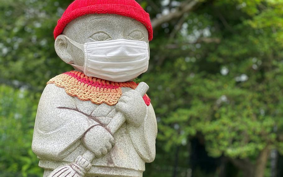 A mask-wearing statue sits atop Mount Takao, a popular hiking spot near Camp Zama and Yokota Air Base, Japan, Saturday, June 27, 2020.