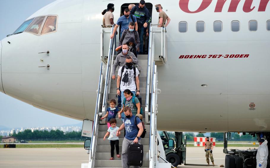 Passengers exit a Patriot Express flight at Osan Air Base, South Korea, June 10, 2020.