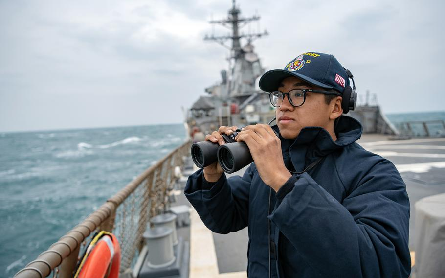 A sailor stands lookout on the flight deck of the guided-missile destroyer USS Barry as it traverses the Taiwan Strait on April 23, 2020.
