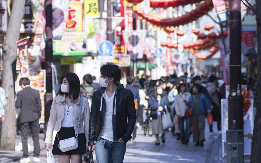 Tourists stroll through Chinatown in Yokohama, Japan, March 18, 2020.