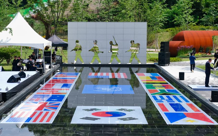 Flags of the nations that fought for the Allies in the Korean War are displayed in a pond during a memorial service at Osan Jukmiryeong Peace Park in Osan, South Korea, Sunday, July 5, 2020.
