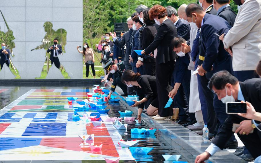 People release paper boats, made by children, into a pond as a proclamation of peace during a Korean War memorial service at Osan Jukmiryeong Peace Park in Osan, South Korea, Sunday, July 5, 2020.