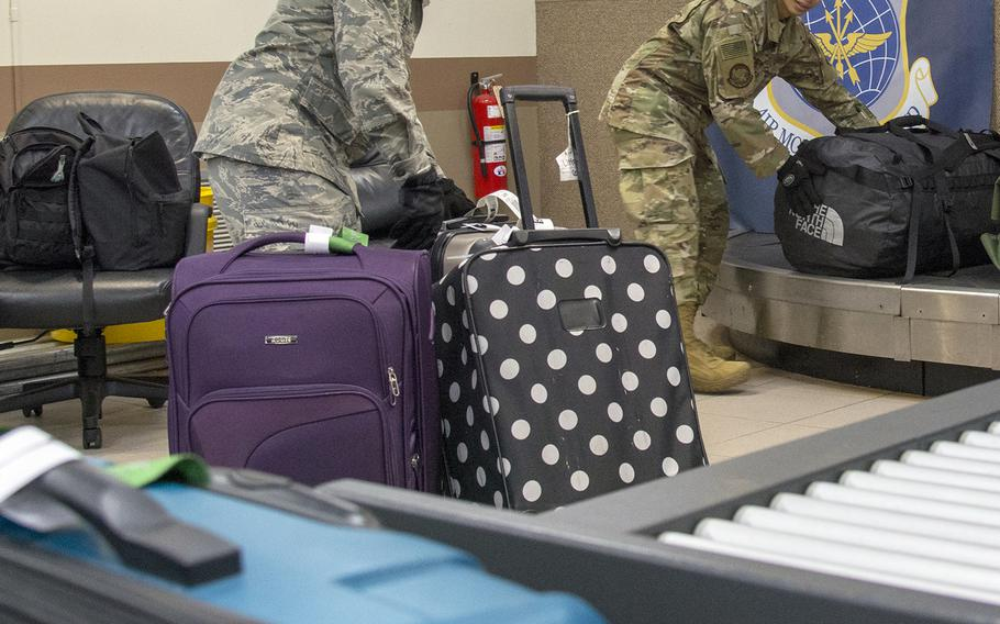 Airmen move baggage onto a conveyor belt ahead of a Patriot Express flight at Andersen Air Force Base, Guam, March 7, 2020.