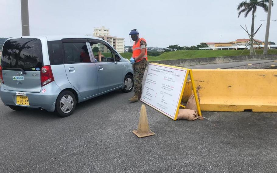 A gate guard checks a driver's temperature outside Camp Foster, Okinawa, in this image posted to the base Facebook page on May 17, 2020.
