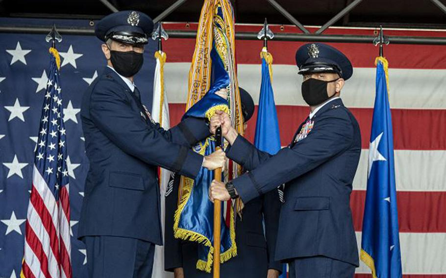 Lt. Gen. Kevin Schneider, commander of U.S. Forces Japan and 5th Air Force, left, passes a guidon to new 35th Fighter Wing commander Col. Jesse Friedel, during a ceremony at Misawa Air Base, Japan, Monday, July 13, 2020.