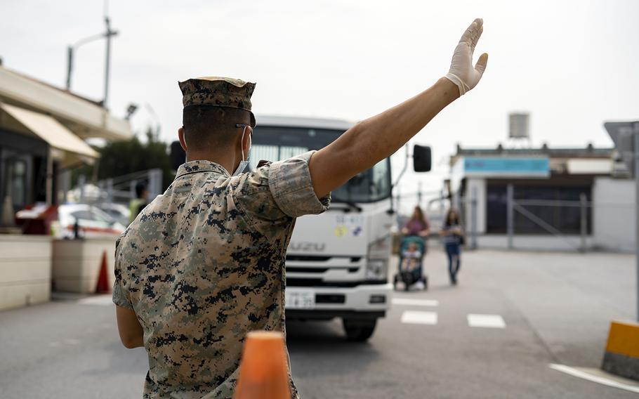 Marines conduct health and wellness checks for people entering Camp Foster, Okinawa, April 3, 2020.