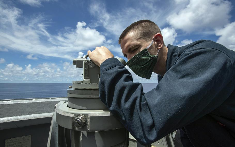 Aboard the guided-missile destroyer USS Ralph Johnson, Petty Officer 2nd Class Paul Vance scans the horizon near the Spratly Islands in the South China Sea, July 14, 2020.