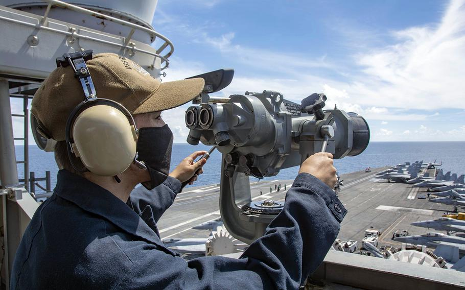 Seaman Alexander Chitty stands forward lookout watch on the signal bridge of the aircraft carrier USS Ronald Reagan in the South China Sea, July 16, 2020.