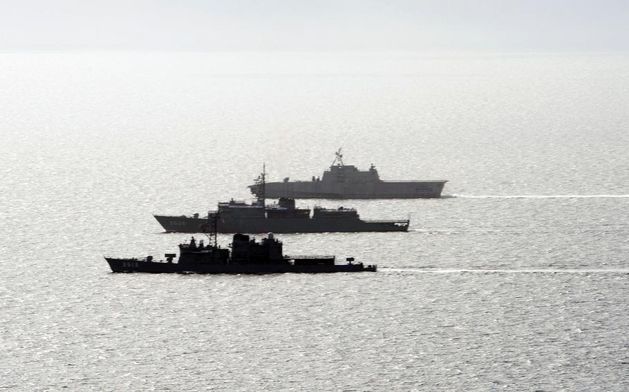The Japan Maritime Self-Defense Force ships JS Kashima, bottom, and JS Shimayuki, center, train alongside the littoral combat ship USS Gabrielle Giffords in the South China Sea, June 23, 2020.