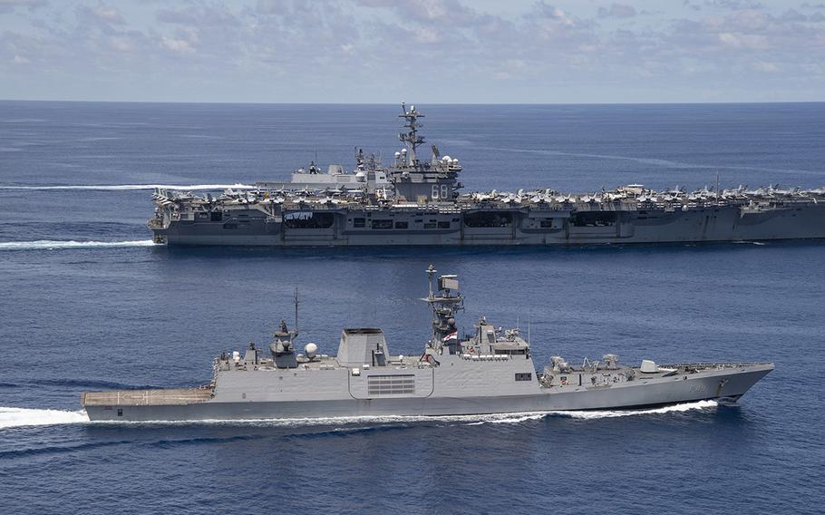 The USS Nimitz steams beside a ship from the Indian navy in the Indian Ocean, Monday, July 20, 2020.