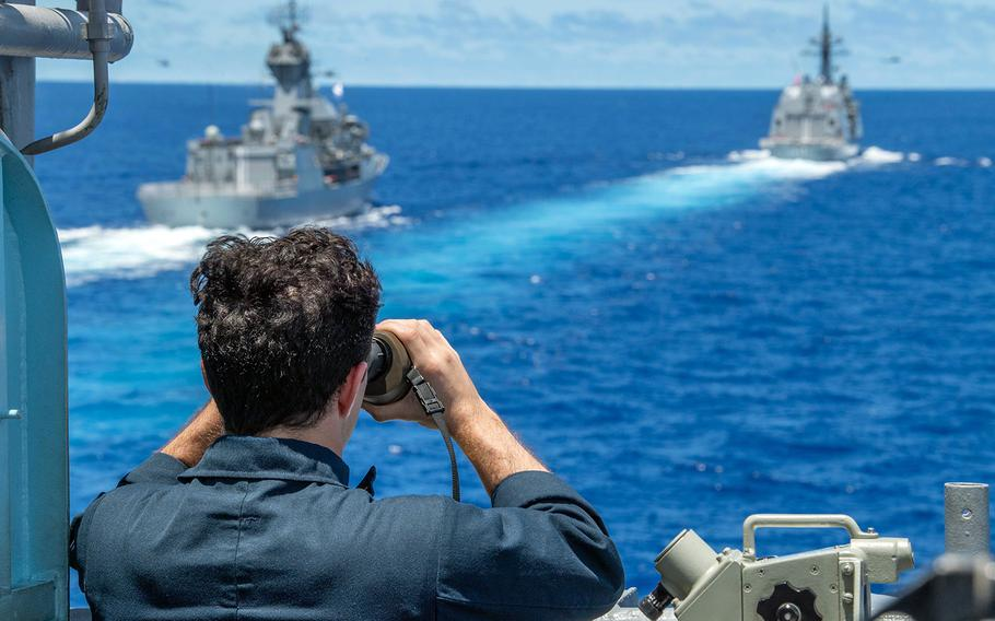 Ens. David Falloure of the guided-missile cruiser USS Antietam uses a rangefinder to determine the distance to Australia's HMAS Stuart, left, and Japan's JS Teruzuki in the South China Sea, July 21, 2020.