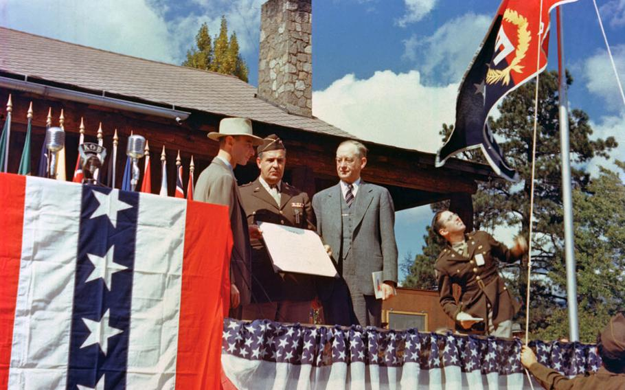 """Gen. Leslie Groves, center, head of the Manhattan Project, presents the Army-Navy """"E"""" Award flag to the Los Alamos laboratory with lab director J. Robert Oppenheimer, left, and University of California President Robert Sproul present on Oct. 16, 1945."""