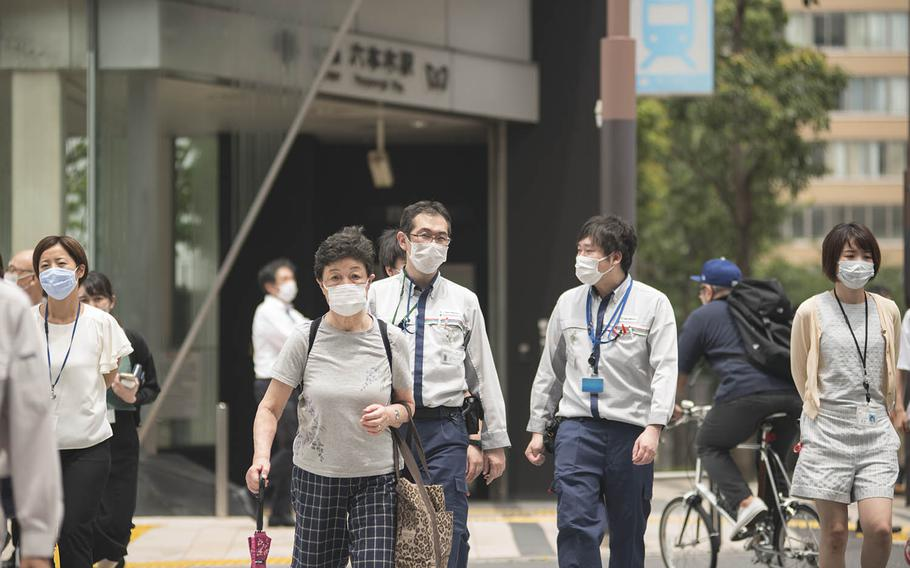 Pedestrians cross a street outside Roppongi Station in central Tokyo, July 21, 2020.