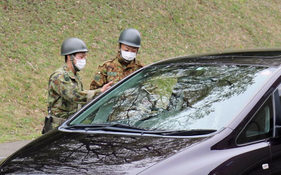 Japan Ground Self-Defense Force personnel screen people for coronavirus symptoms at Camp Zama, Japan, March 31, 2020.