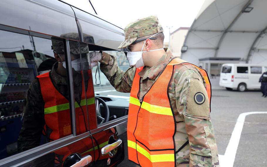 A soldier takes the temperature of a driver at Camp Zama, Japan, March 31, 2020.