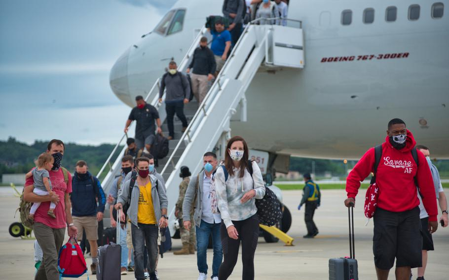 Service members and their family members exit a Patriot Express flight after arriving at Osan Air Base, South Korea, on July 14, 2020.