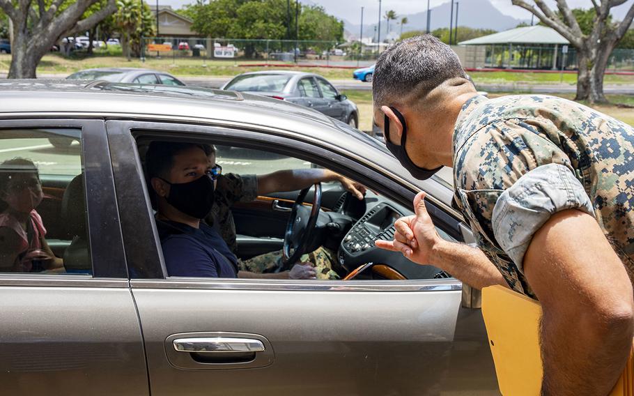 Col. Speros Koumparakis, commander of Marine Corps Base Hawaii, greets a family outside Mokapu Elementary School on base, July 28, 2020.