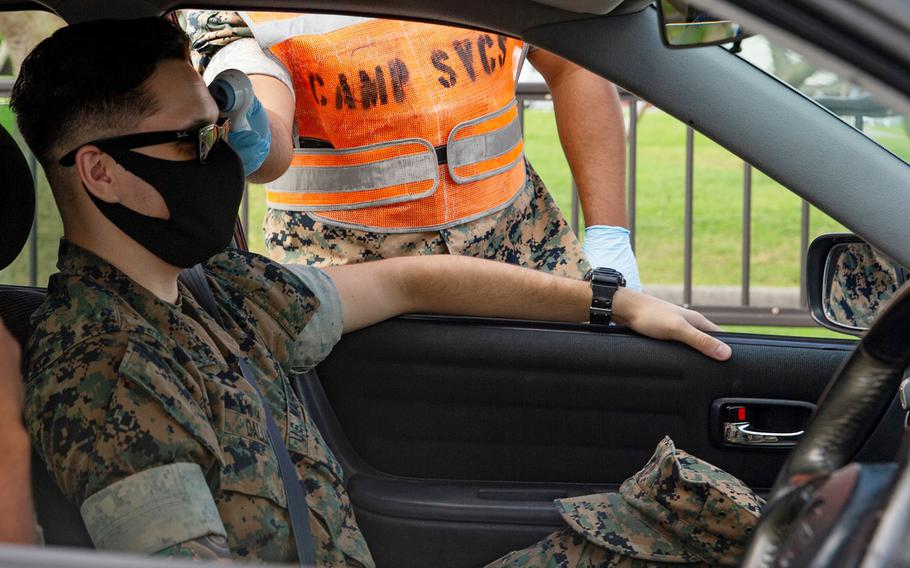 A Marine's temperature is taken before driving onto Camp Foster, Okinawa, July 29, 2020.