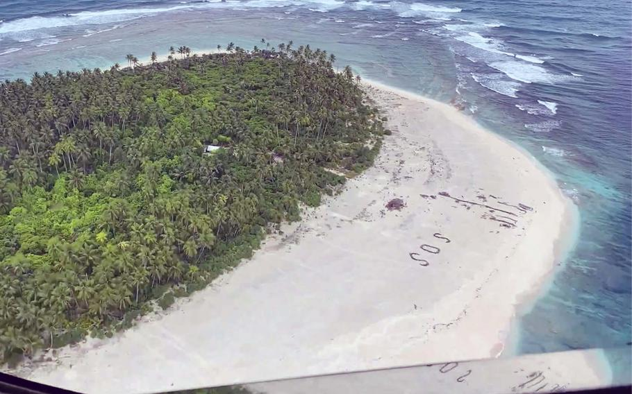 An SOS in the sand can be seen in this screenshot taken from a DVIDS video. Guardsmen locate three missing mariners on Pikelot Island during a search and rescue mission in the Federated States of Micronesia southwest of Guam, Aug. 2, 2020.