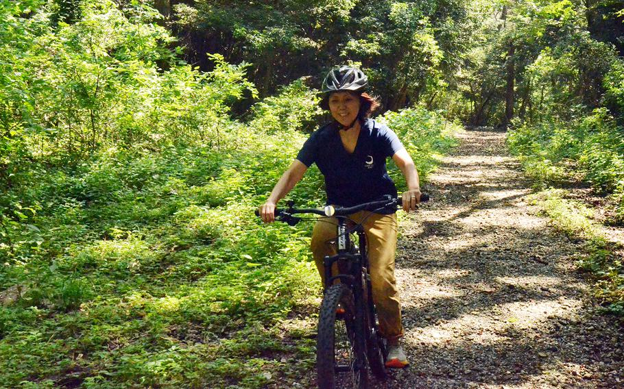 Tama Hills Recreation Center employee Yuki Ono takes an electric mountain bike for a spin on the center's trails in western Tokyo, Thursday, Aug. 6, 2020.