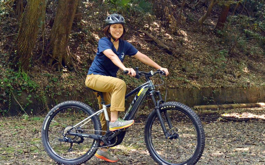 Tama Hills Recreation Center employee Yuki Ono poses on an electric mountain bike on one of the center's trails in western Tokyo, Thursday, Aug. 6, 2020.
