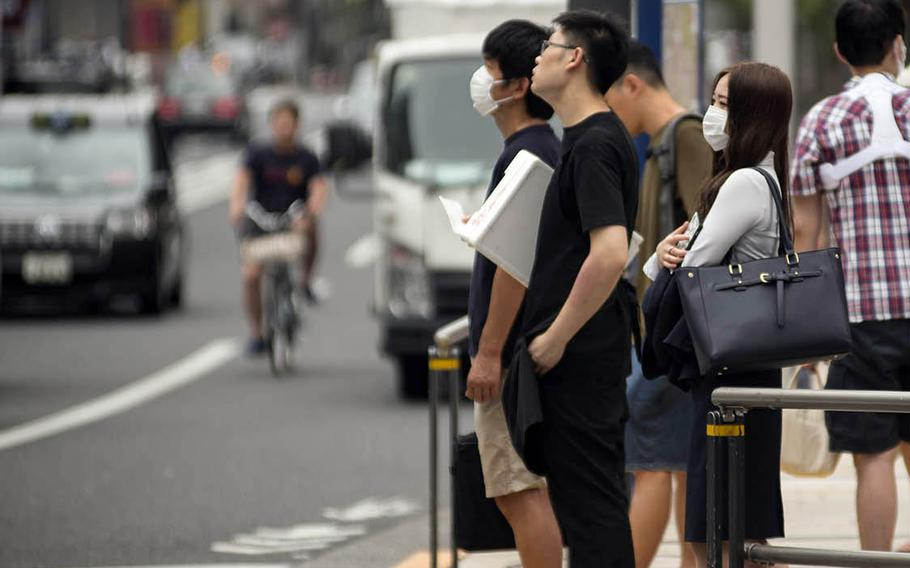 Pedestrians wait to cross a busy street in the Roppongi district of central Tokyo, July 21, 2020.